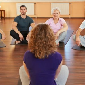 16490277 - fitness coach giving group yoga instructions in a gym
